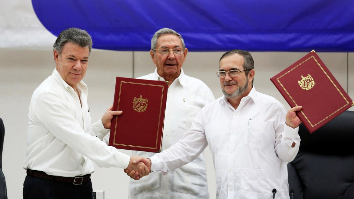 Colombia's President Juan Manuel Santos, left, shakes hands with FARC rebel leader Rodrigo Londono, better known by his nom de guerre Timochenko, right, as Cuba's President Raul Castro looks on after the signing of a historic ceasefire deal between the Colombian government and FARC rebels in Havana, Cuba, on June 23, 2016. Credit: Reuters