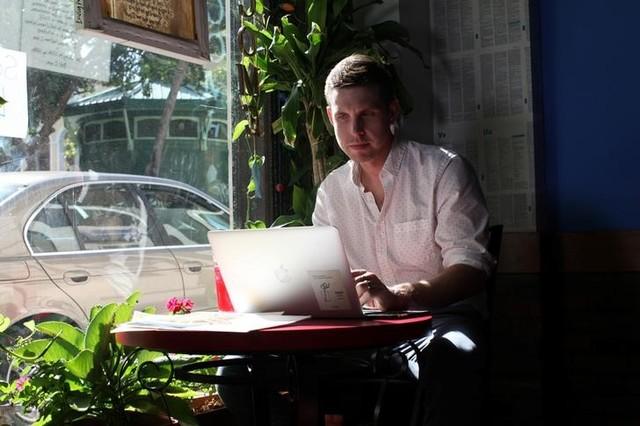 Reuters journalist Nick Brown works at his laptop at a cafe in San Juan, Puerto Rico, August 8, 2016. Credit: Reuters/Alvin Baez