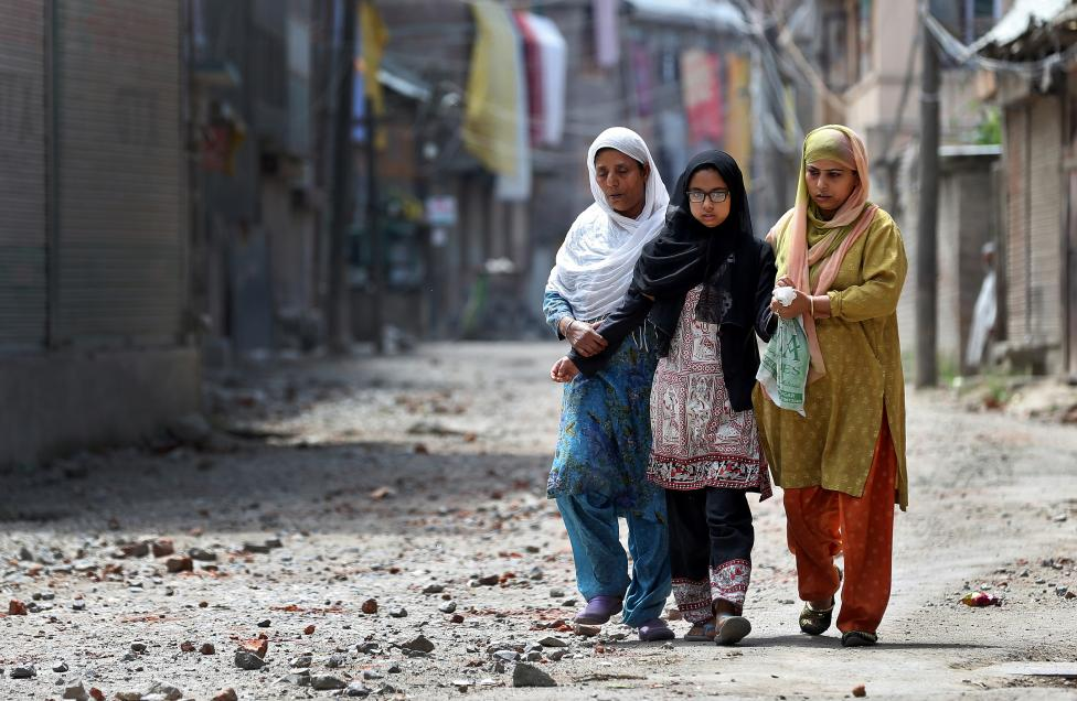 Two women and a girl make their way along a street littered with rocks thrown by protestors in Srinagar as the city remains under curfew following weeks of violence in Kashmir August 19, 2016. Credit: Cathal McNaughton/Reuters/ File Photo