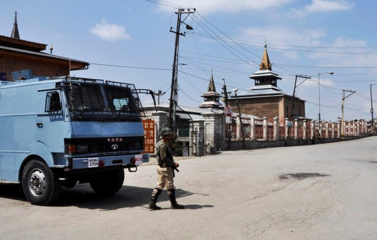 A security jawan stands guard on a deserted street near Jamia Masjid during the 66th day of restrictions and strike in Srinagar on Monday. Credit: PTI