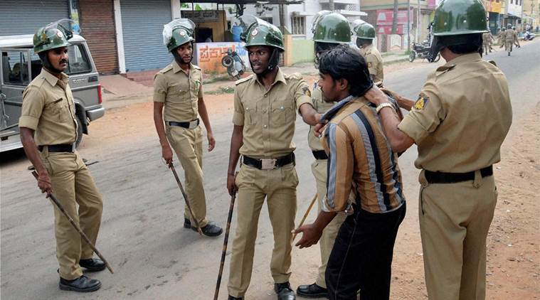 Mandya: Police arrest a miscreant during a protest by Kannada people over Cauvery water row, in Mandya district on Monday. Credit: PTI