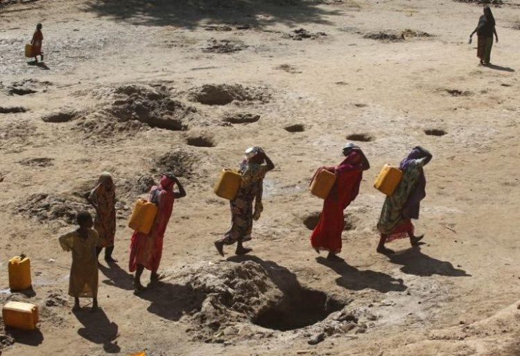 Women carry jerry cans of water from shallow wells dug from the sand along the Shabelle River bed, which is dry due to drought in Somalia's Shabelle region, March 19, 2016. REUTERS/Feisal Omar/Files