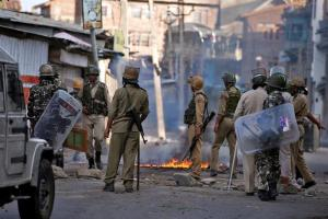 Indian policemen stand next to a burning handcart set on fire by demonstrators during a protest in Srinagar against the recent killings in Kashmir, July 18, 2016. Credit: Reuters/Danish Ismail/Files