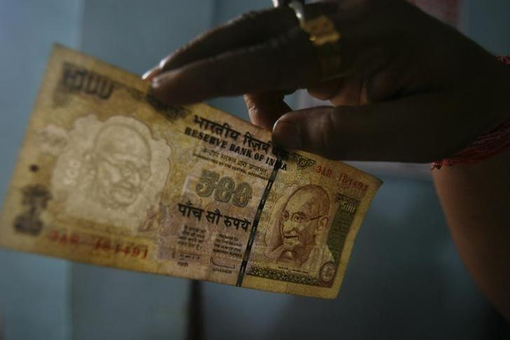 An employee checks a Rs 500 note at a cash counter inside a bank in Agartala August 9, 2011. Credit: Reuters/Jayanta Dey/Files