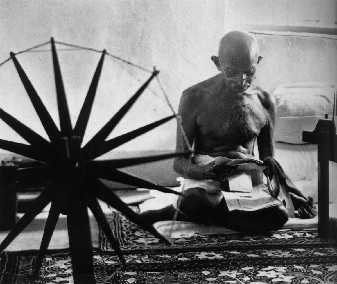 Gandhi reading next to his spinning wheel. Credit: eBay