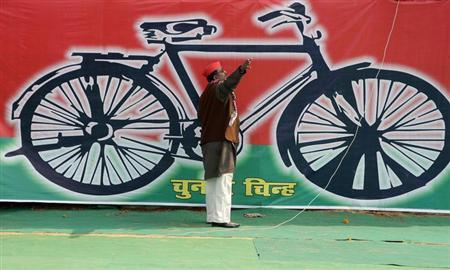 A Samajwadi Party worker gestures in front of a banner with the party's electoral symbol, the bicycle. Credit: Reuters/Jitendra Prakash/Files