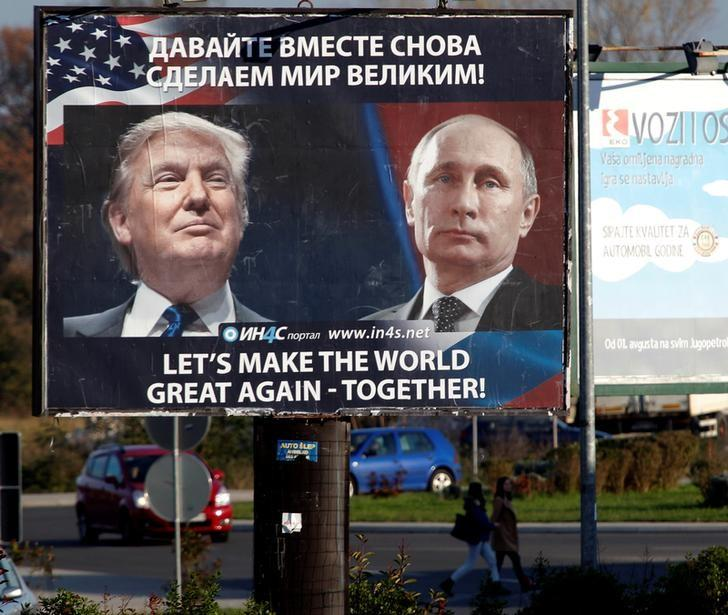 Pedestrians cross the street behind a billboard showing a pictures of US President Donald Trump and Russian President Vladimir Putin in Danilovgrad, Montenegro, November 16. 2016. Credit: Reuters