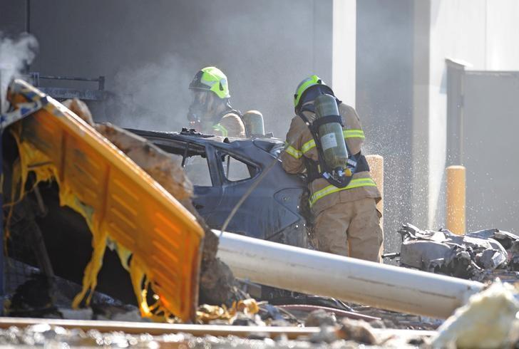 Emergency services personnel are seen at the scene of a plane crash in Essendon in Melbourne, Australia, February 21, 2017. Credit: Joe Castro/Reuters