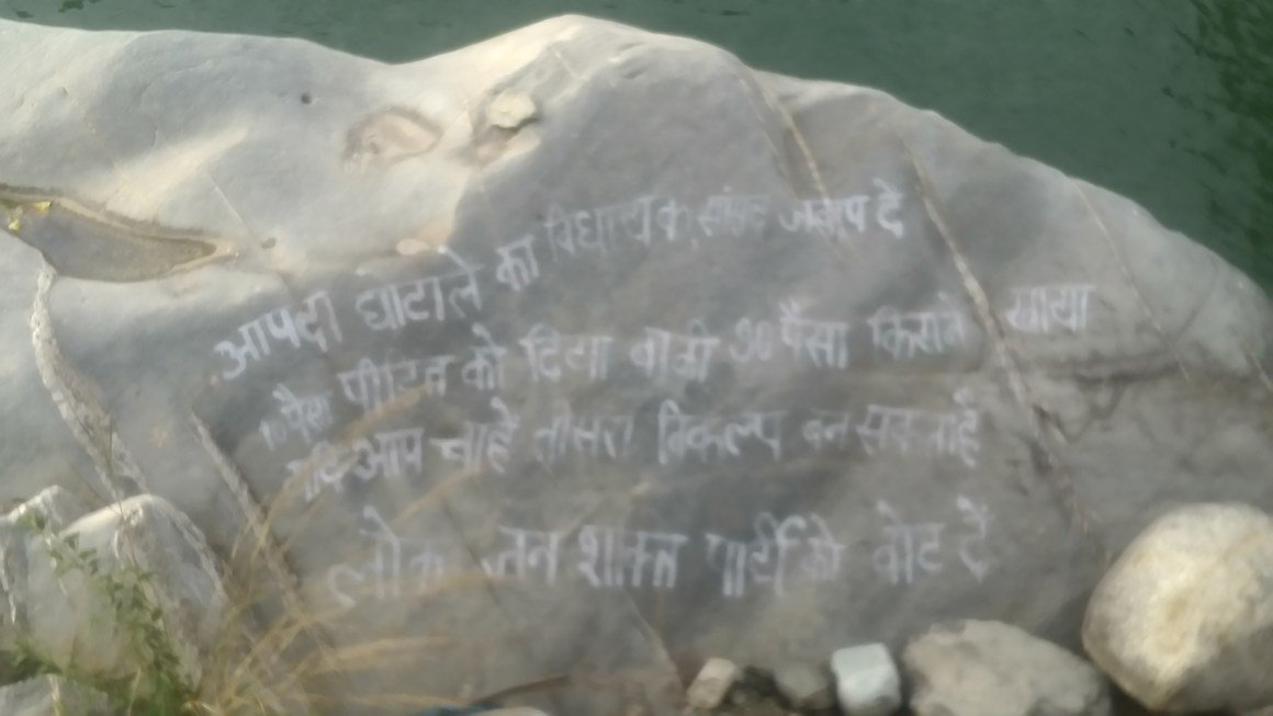 This message on a rock alongside river Mandakini by a political party in the Augustmuni town reveals how corruption in flood rehabilitation remains the main election issue in this region. Credit: Gaurav Vivek Bhatnagar