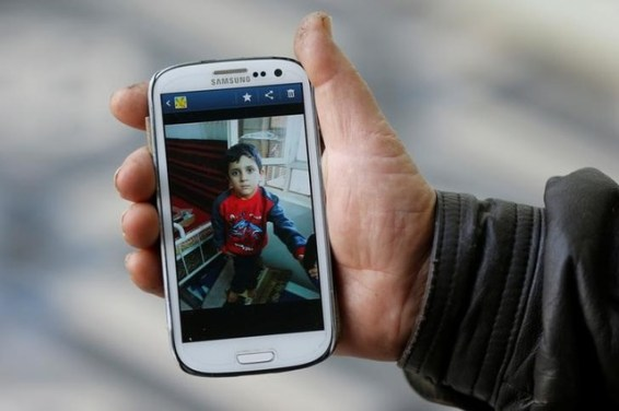 Abu Ahmed, who bought Yazidi boy Ayman from ISIS militants in Mosul, shows a picture of Ayman on his phone in Rashidiya, north of Mosul, Iraq, January 30, 2017. Credit: Reuters