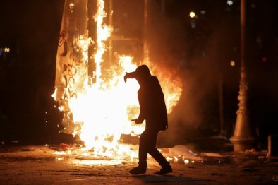 A protester walks in front of a burning street sign during scuffles with police at a demonstration in Bucharest, Romania, February 1, 2017. Credit: Reuters