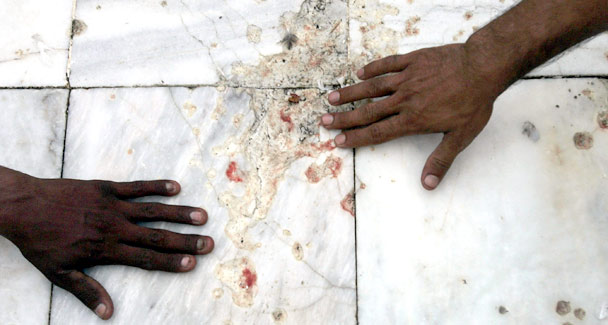 Devotees touch the blood-stained marble floor of the Data Darbar Sufi shrine in Lahore, July 2, 2010, hours after dozens died from a suicide bomb blast. Credit: Reuters