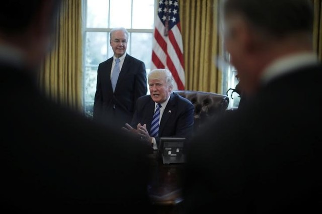 US President Donald Trump talks to journalist at the Oval Office of the White House after the AHCA health care bill was pulled before a vote, accompanied by US Health and Human Services Secretary Tom Price (L) and Vice President Mike Pence (not pictured), in Washington, US, March 24, 2017. Credit: Reuters/Carlos Barria
