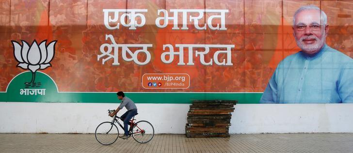 A worker of the Bharatiya Janata Party (BJP) rides his bicycle past the party's campaign billboard featuring Prime Minister Narendra Modi outside their party headquarters in New Delhi, India, February 10, 2015. Credit: Reuters/Anindito Mukherjee/File Photo