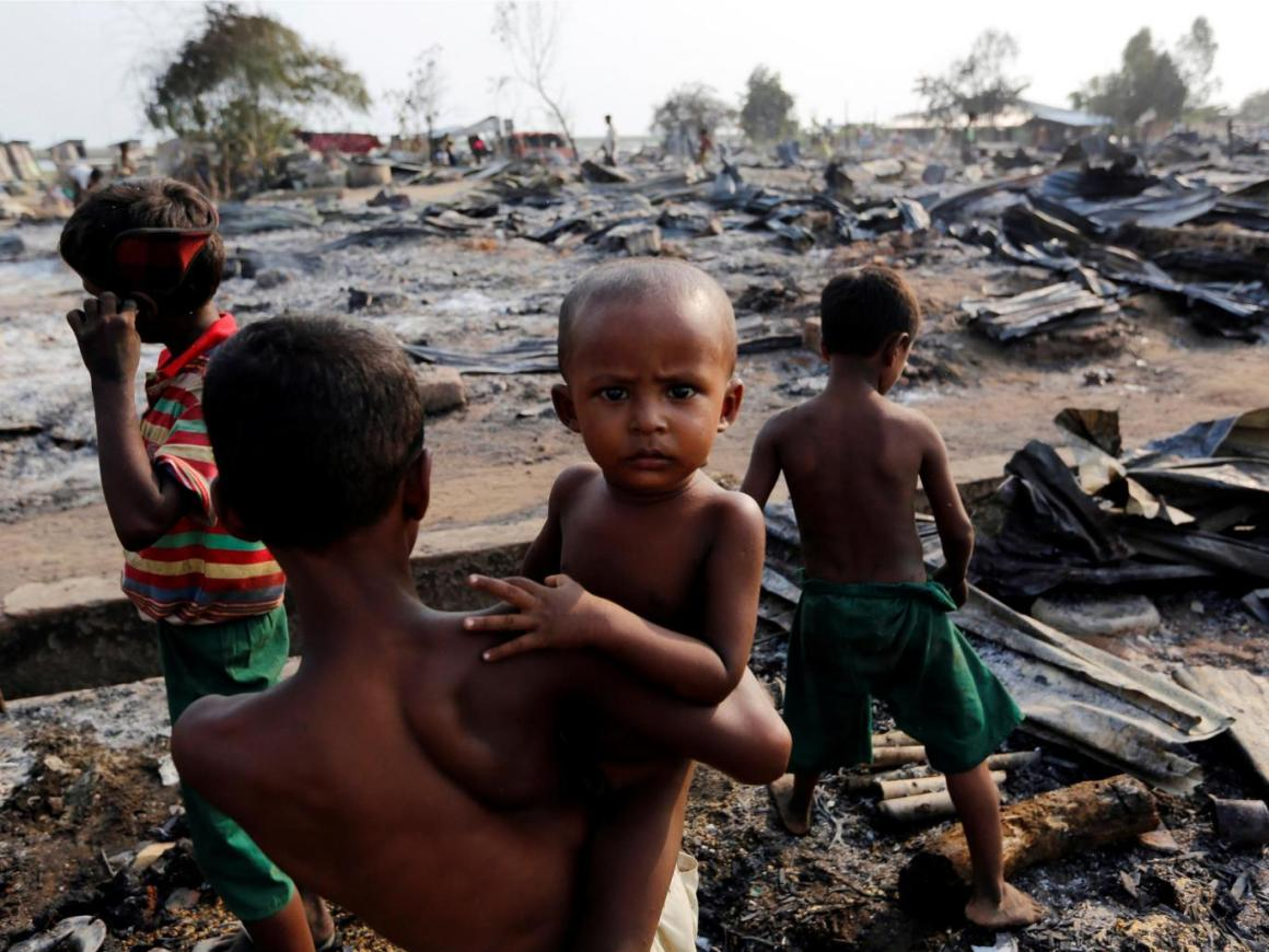 Boys stand among debris after fire destroyed shelters at a camp for internally displaced Rohingya Muslims in the western Rakhine State near Sittwe. Credit: Reuters