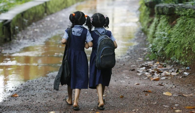 Seven year old twins Shahana (R) and Shahala (L) walk to their school in Kodinji village in the southern Indian city of Kerala July 28, 2009. REUTERS/Arko Datta/Files