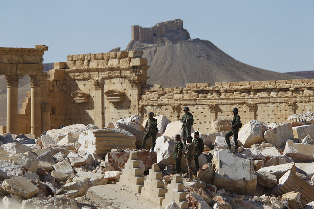 Syrian army soldiers stand on the ruins of the Temple of Bel in the historic city of Palmyra, in Homs Governorate, Syria April 1, 2016. Credit: Reuters
