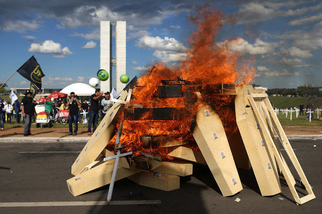 Striking police officers set fire to coffins during a protest by Police officers from several Brazilian states against pension reforms proposed by Brazil's president Michel Temer, in Brasilia, Brazil April 18, 2017. Credit: Reuters/Adriano Machado