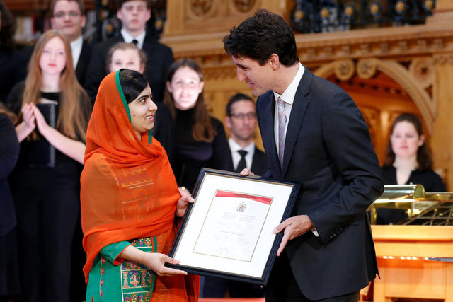 Canada's Prime Minister Justin Trudeau (R) presents Pakistani Nobel Peace Prize laureate Malala Yousafzai with honourary Canadian citizenship during a ceremony in the Library of Parliament on Parliament Hill in Ottawa, Ontario, Canada, April 12, 2017. Credit: Reuters/Chris Wattie
