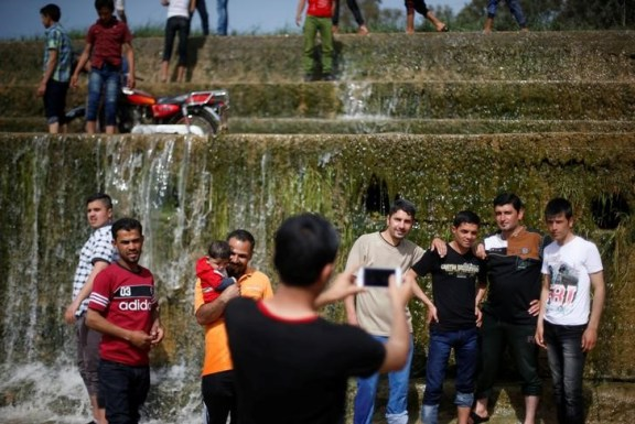 "Iraqi people take pictures as they enjoy their Friday holiday at Shallalat district (Arabic for ""waterfalls"") in eastern Mosul, Iraq, April 21, 2017. Credit: Reuters/ Muhammad Hamed"