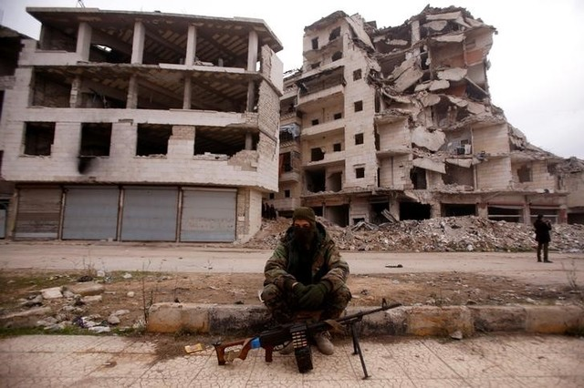 A member of forces loyal to Syria's President Bashar al-Assad sits near damaged buildings in Aleppo's Salaheddine district, Syria December 16, 2016. Credit: Reuters/Omar Sanadiki