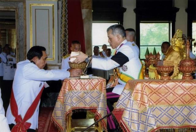Thailand's King Maha Vajiralongkorn Bodindradebayavarangkun (R) returns the constitution after signing it to Thailand's Prime Minister Prayut Chan-o-cha at Ananta Samakhom Throne Hall in Bangkok, Thailand April 6, 2017. Credit: Reuters