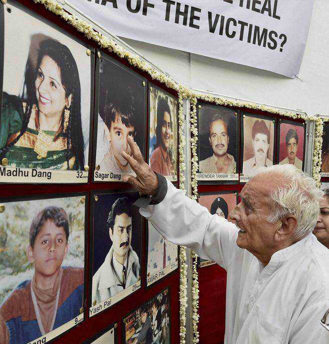 An elderly man looks at the photographs of Uphaar fire tragedy victims in New Delhi. Credit: PTI