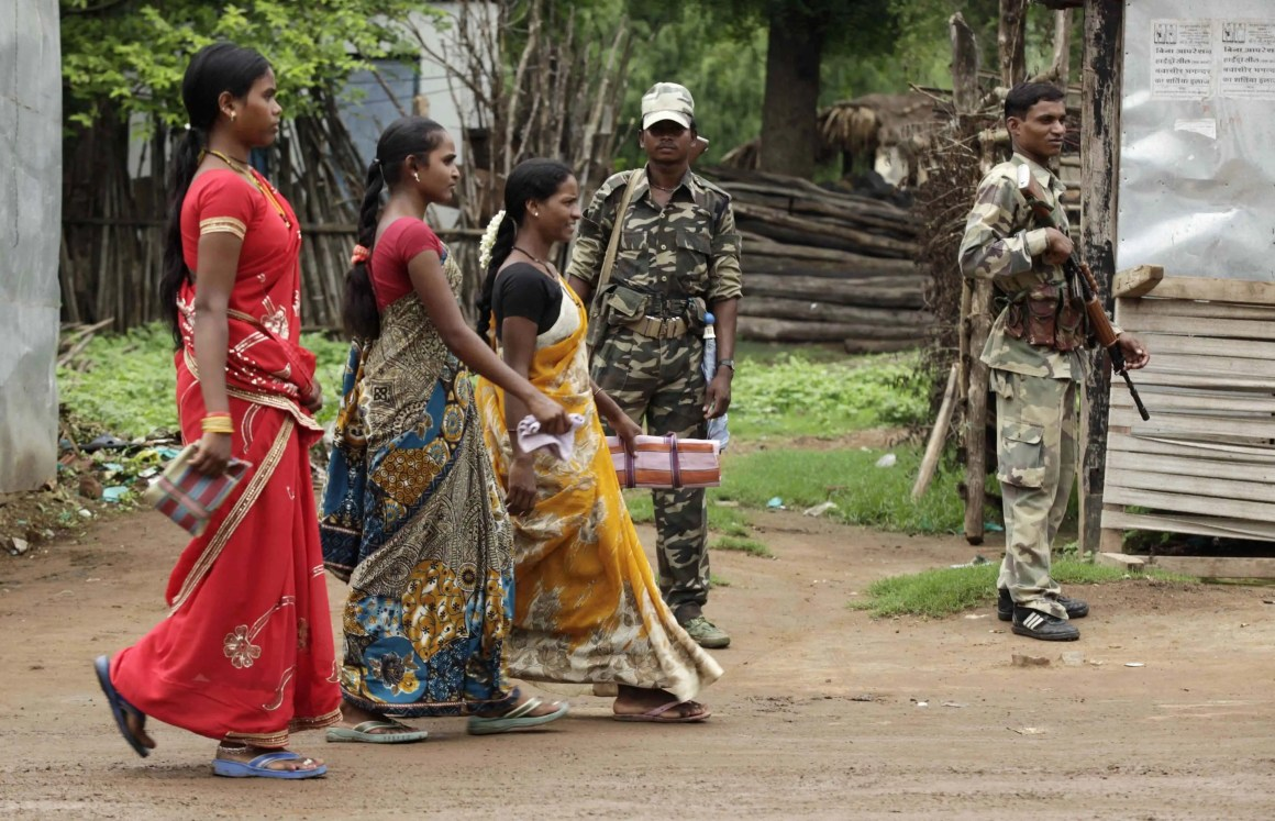 Women in Awapalli village walk past members of the security forces. Credit: Rupak De Chowdhuri/Reuters