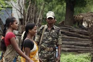 Women in Awapalli village walk past members of the security forces. Credit: Rupak De Chowdhuri/Reuters