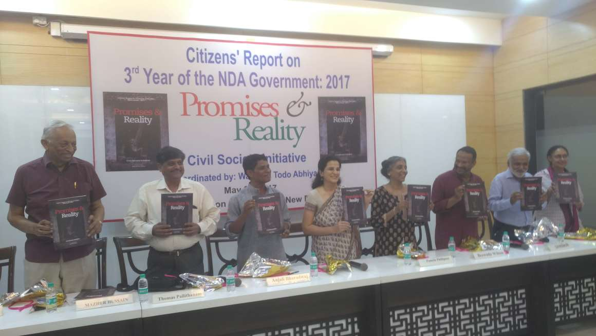 Panelists holding up copies of the report. Credit: Akhil Kumar