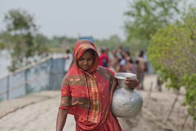 A woman carries a container of drinking water in the coastal area of Bangladesh. Credit: Rafiqul Islam/IPS