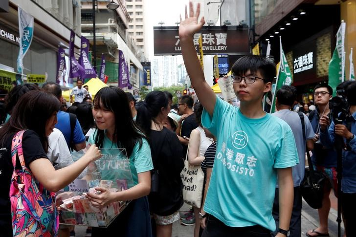 Pro-democracy activist Joshua Wong waves to pro-democracy protesters during a march marking the 20th anniversary of Hong Kong's handover to Chinese sovereignty from British rule, in Hong Kong, China, July 1, 2017. Credit: Reuters/Tyrone Siu