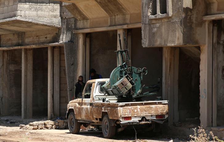 Free Syrian Army fighter stand near an anti-air craft machine gun in Quneitra, Syria July 8, 2017. Credit: Reuters/Alaa al-Faqir
