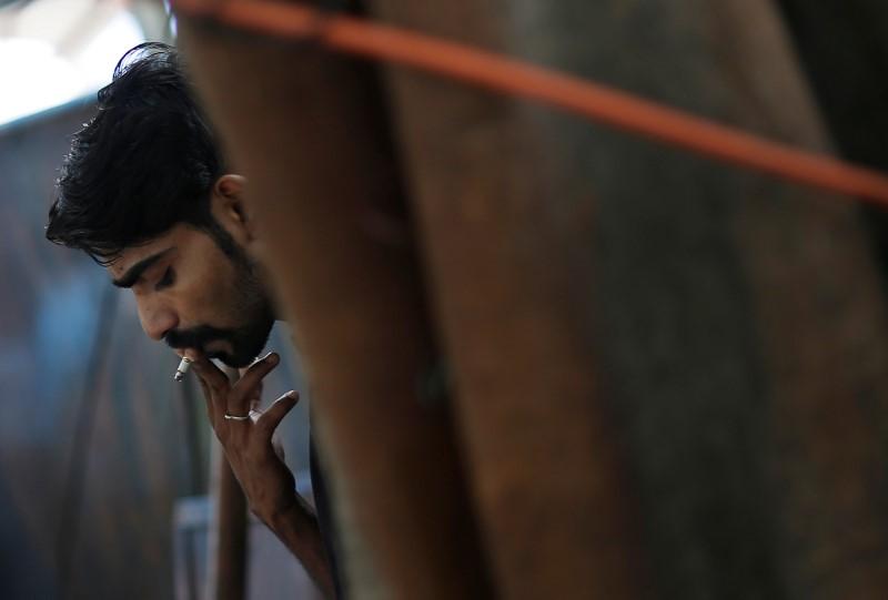 A man smokes a cigarette along a road in New Delhi, India, July 14, 2017. Credit: Reuters/Adnan Abidi