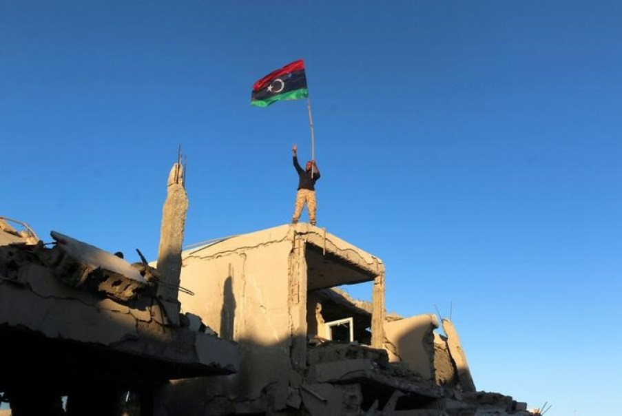 A fighter of Libyan forces allied with the UN-backed government waving a Libyan flag flashes victory sign as he stands atop the ruins of a house after forces finished clearing Ghiza Bahriya, the final district of the former ISIS stronghold of Sirte, Libya December 6, 2016. Credit: Reuters/Hani Amara