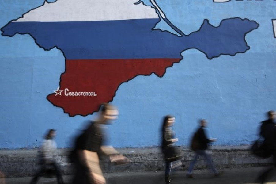 People pass a mural showing a map of Crimea in the Russian national colours on a street in Moscow March 25, 2014. Credit: Reuters/Artur Bainozarov