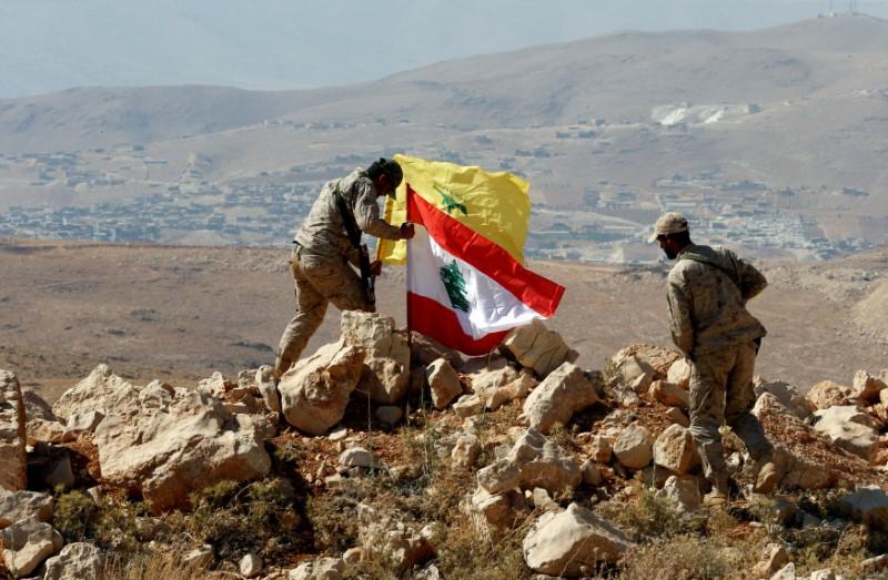Hezbollah fighters put Lebanese and Hezbollah flags at Juroud Arsal, Syria-Lebanon border, July 25, 2017. Credit: Reuters/Mohamed Azakir