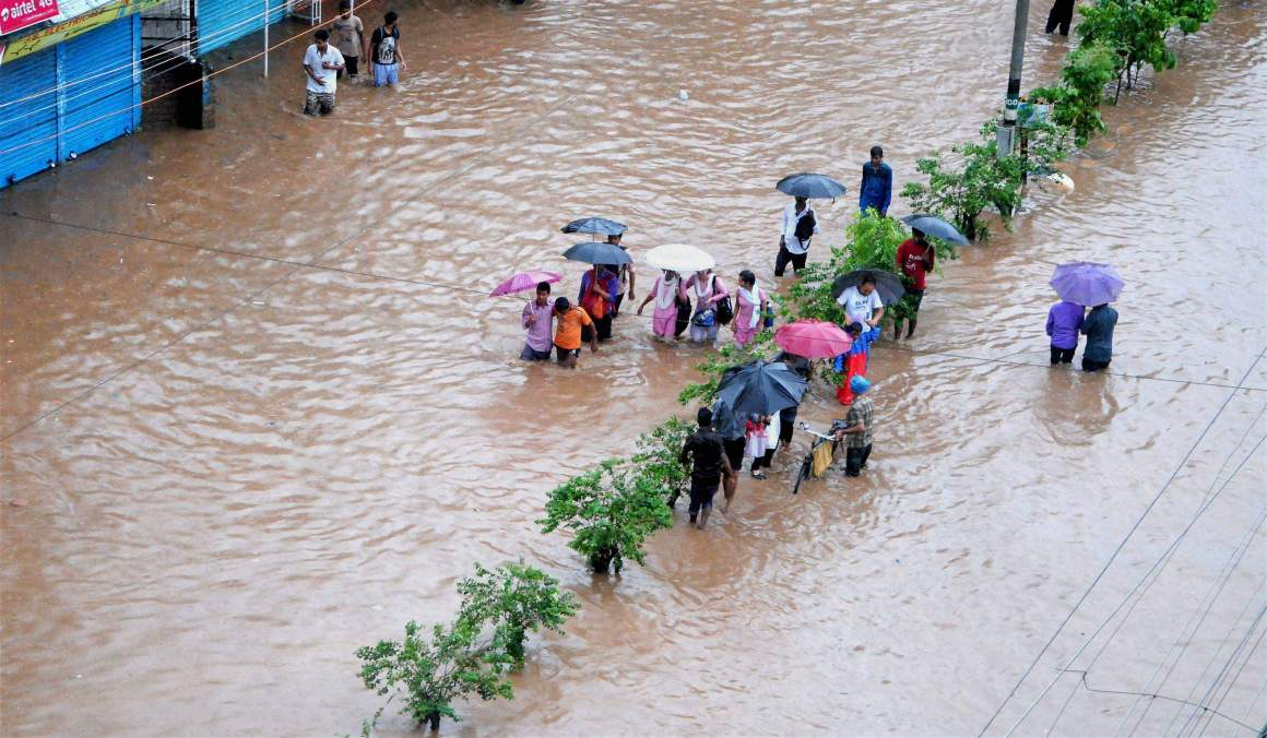 People make their way through a flooded street after heavy rainfall in Guwahati, Assam. Credit: PTI
