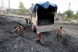 Labourers load coal onto a supply truck on the outskirts of Jammu April 6, 2017. Credit: Reuters/Mukesh Gupta/Files