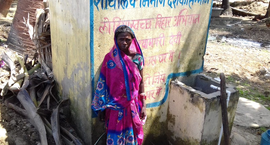 A village woman is standing in front of a newly constructed toilet at her home. Credit: Mohd Imran Khan