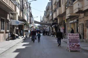 FILE PHOTO: People shop along a street in the city of Homs, Syria in this handout picture provided by SANA on April 7, 2017. Credit: SANA/Handout via Reuters