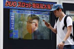 A man walks past a TV set showing North Korea's leader Kim Jong-Un in a news report about North Korea's missile launch in Tokyo, Japan, August 29, 2017. Credit: Reuters/Kim Kyung-Hoon
