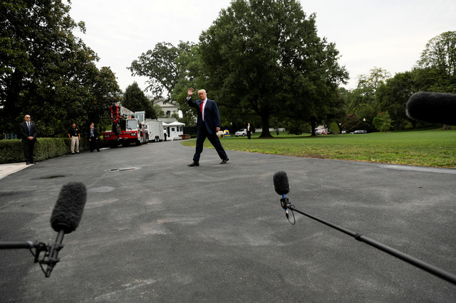 U.S. President Donald Trump waves as he walks past reporters after arriving via Marine One at the White House in Washington, U.S. August 14, 2017. Credit:Reuters