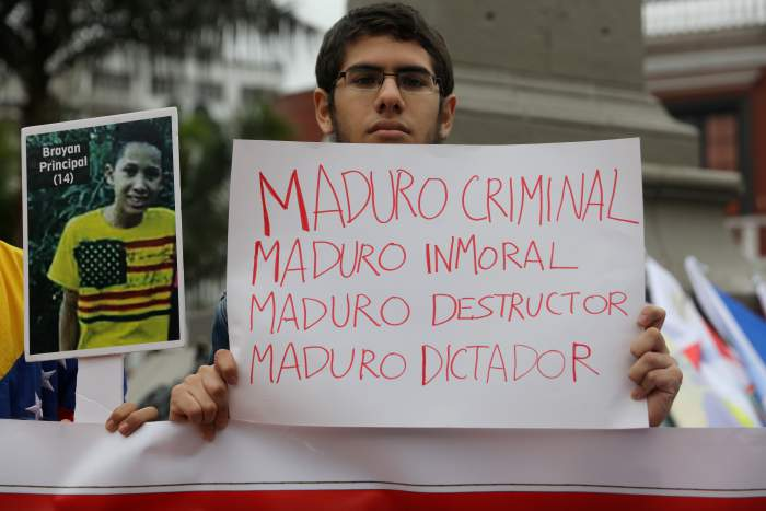 "A demonstrator holds a sign that reads ""Maduro criminal, Maduro unmoral, Maduro wrecker, Maduro dictator"" at a protest against Venezuela's President Nicolas Maduro's government during a meeting of foreign affairs ministers and representatives from across the Americas to discuss issues related to the Venezuelan crisis in Lima, Peru, August 8, 2017. Credit: Reuters/Guadalupe Pardo"
