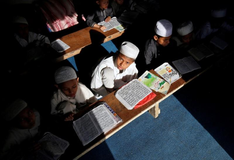 Children belonging to Rohingya Muslim community read the Koran at a madrasa, or a religious school, at a makeshift settlement, on the outskirts of Jammu, May 6, 2017. Credit: Mukesh Gupta