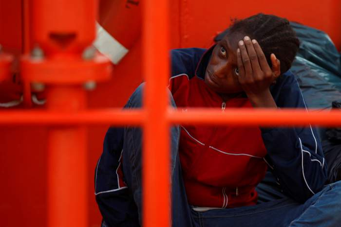 A migrant, who is part of a group intercepted aboard a dinghy off the coast in the Mediterranean sea, reacts on a rescue boat upon arriving at a port in Malaga, Spain August 7, 2017. Credit: Reuters/Jon Nazca