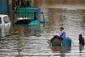 A man uses a makeshift raft to move out of a flooded neighbourhood. Credit: Amit Dave/Reuters
