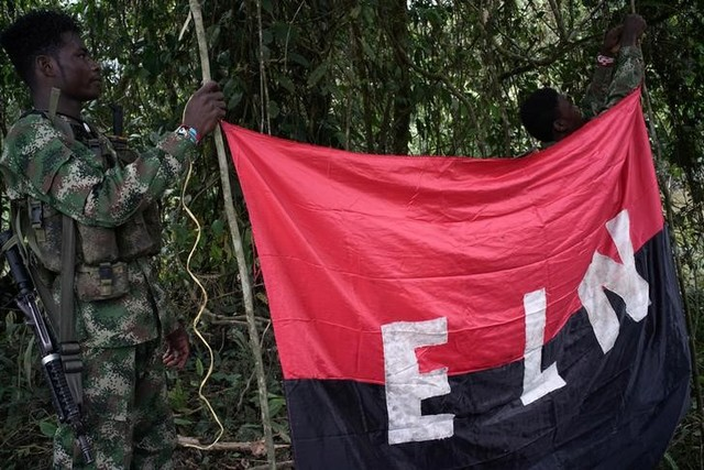 Rebels of the National Liberation Army (ELN) hold a banner in the northwestern jungles in Colombia, August 30, 2017. Credit:Reuters