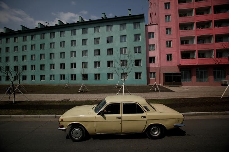 FILE PHOTO: A car drives past residential buildings in Pyongyang April 11, 2012. Credit:Reuters/Bobby Yip/File Photo