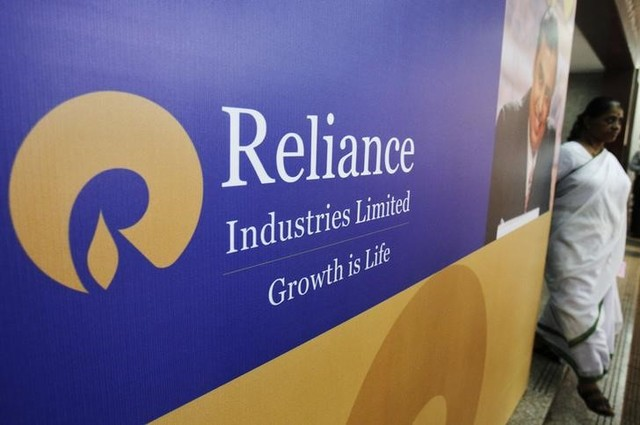 A woman walks past a poster of Reliance Industries installed outside the venue of the company's annual general meeting in Mumbai June 7, 2012. Credit: Reuters/Vivek Prakash/File Photo